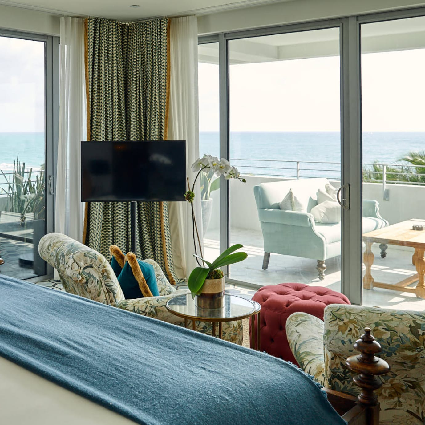 A corner bedroom with views over the sea and a balcony with seating.