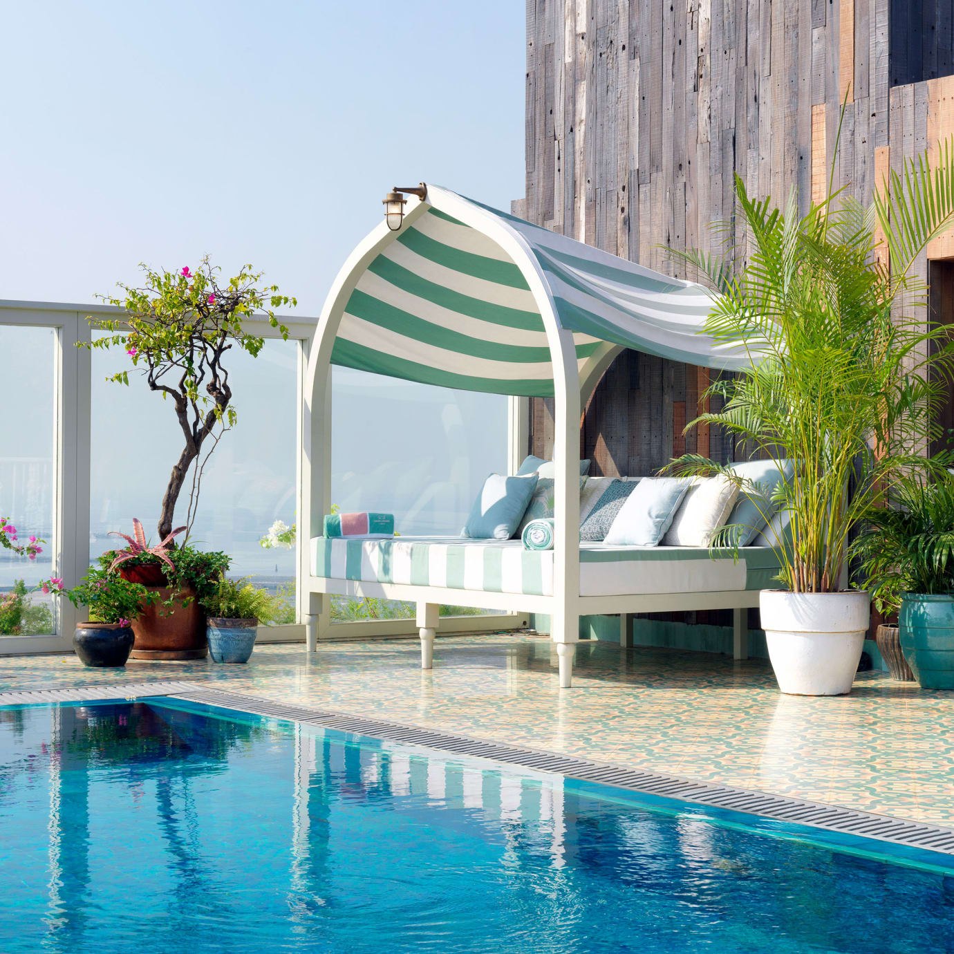 A day bed by a rooftop pool.