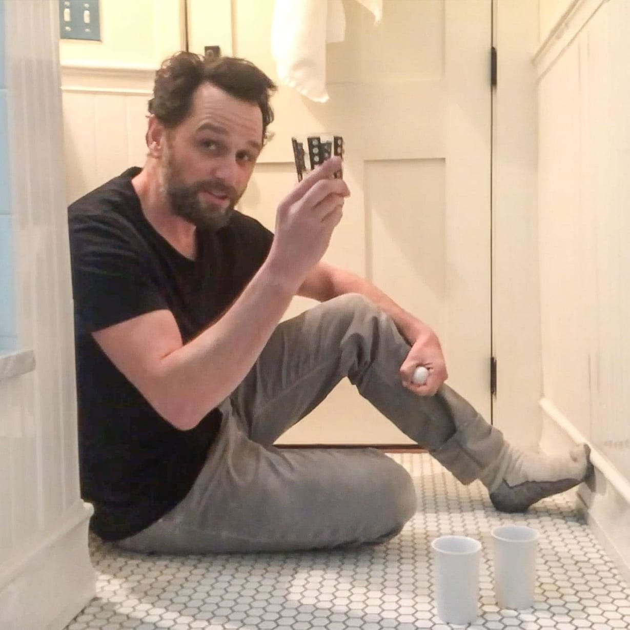 A man sitting on the floor in his bathroom holding up a glass.