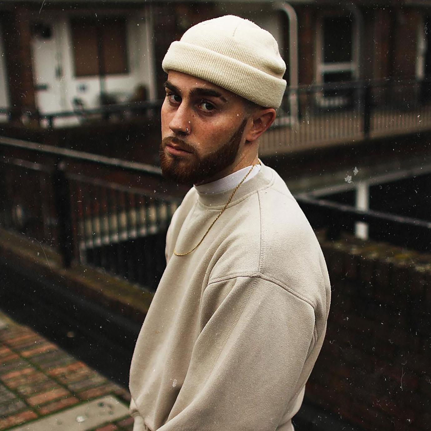 A man with a beard standing on an urban walkway.
