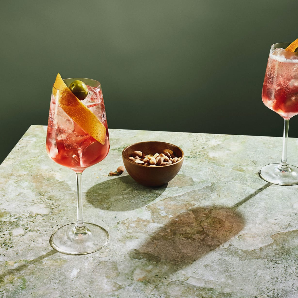 Two glasses with cocktails and bowl of olives