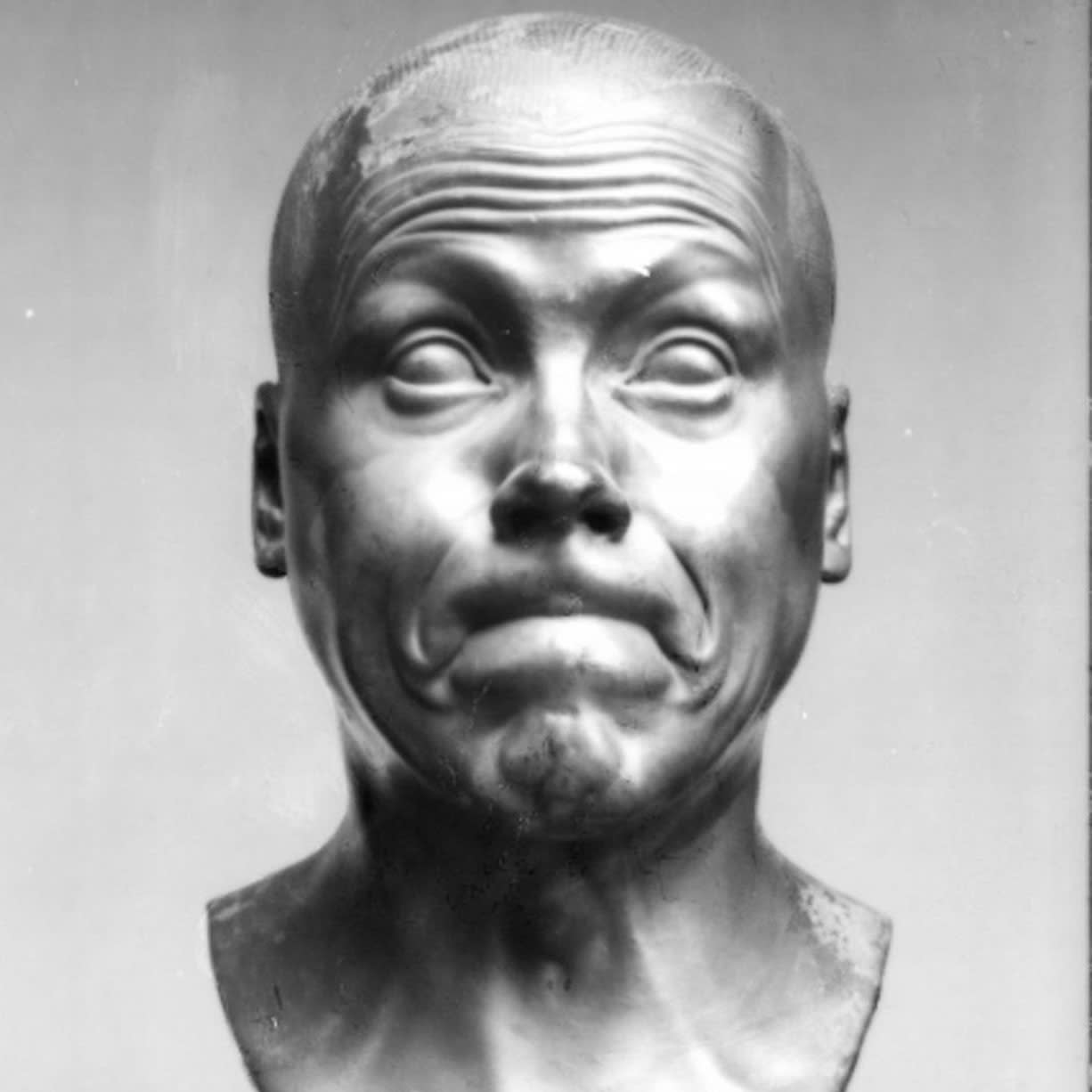 Bust sculpture of man pursing his lips with eyebrows raised