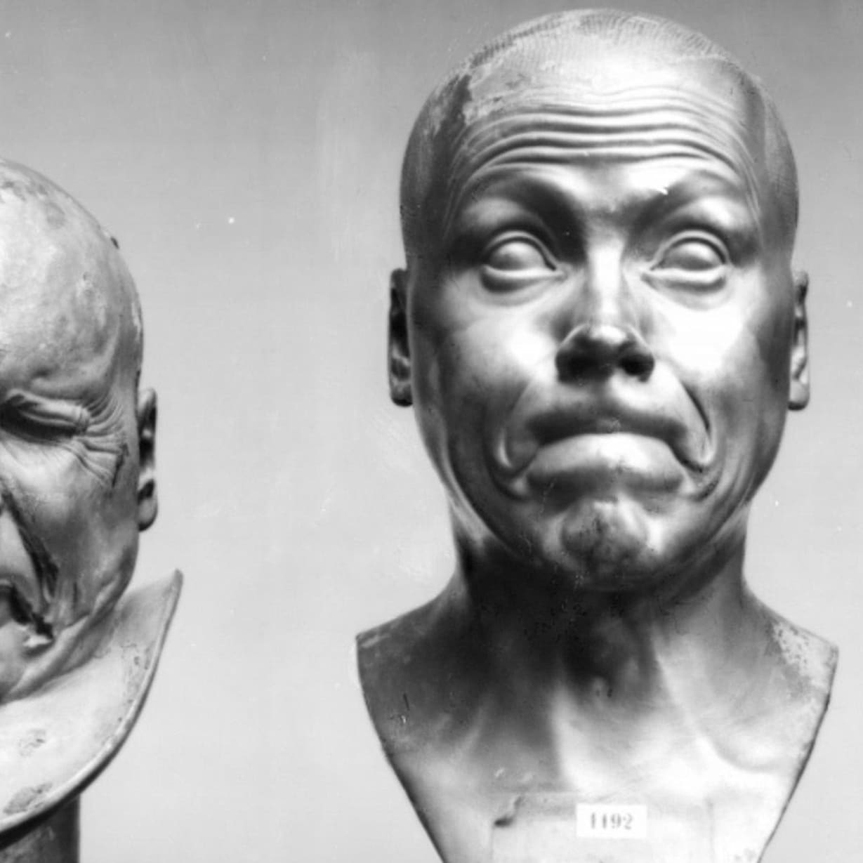 Two metal busts of a man pulling funny faces.