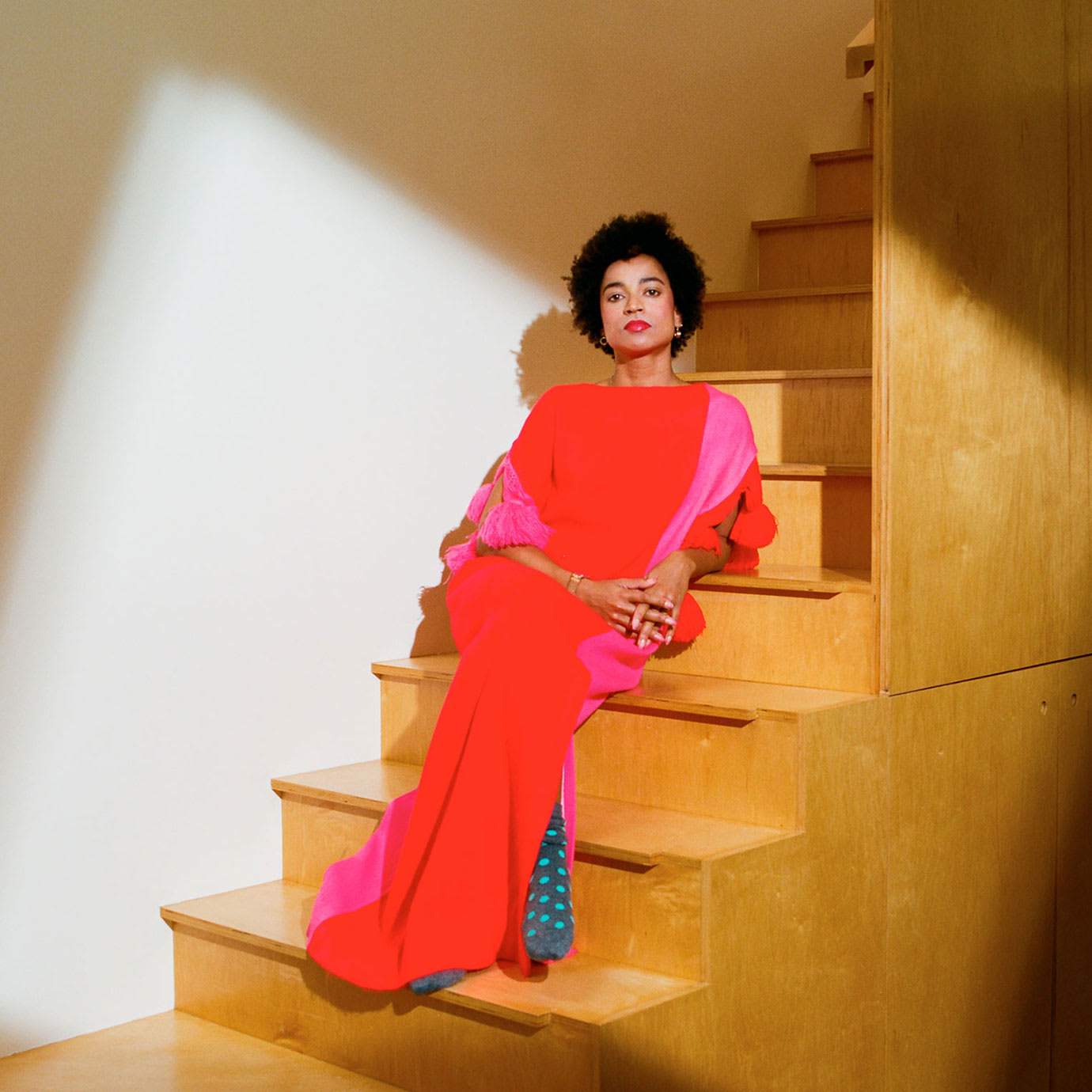 A woman in a red dress reclining on some wooden stairs.