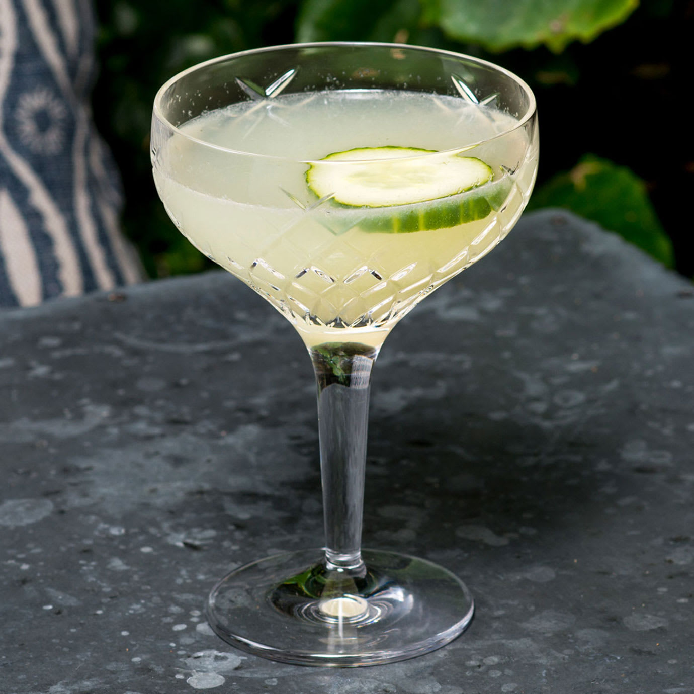 A cocktail with a slice of cucumber in it.