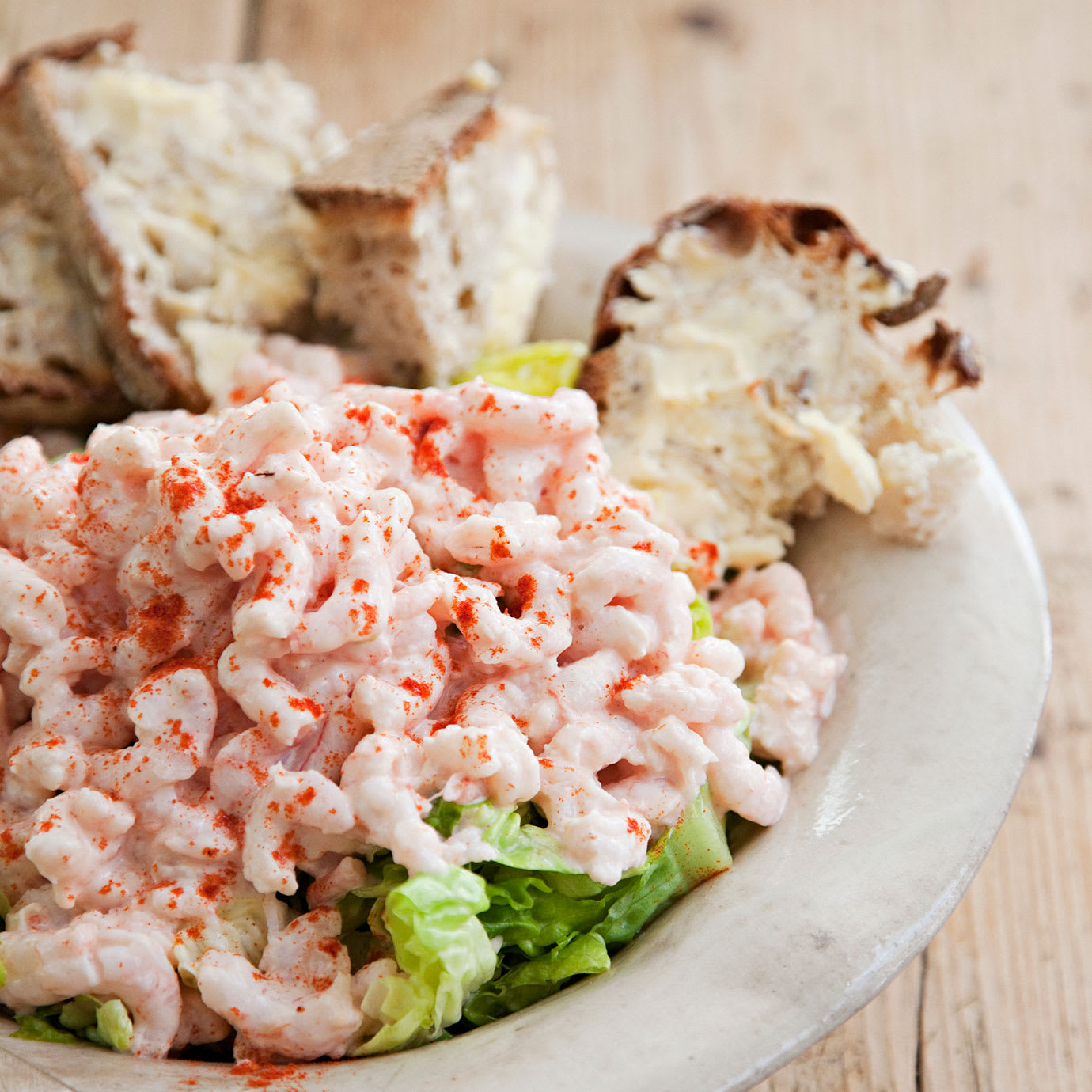 Prawns lettuce and bread on a plate.
