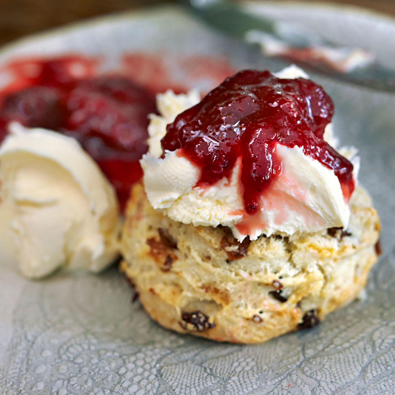 A scone with cream and jam on it.