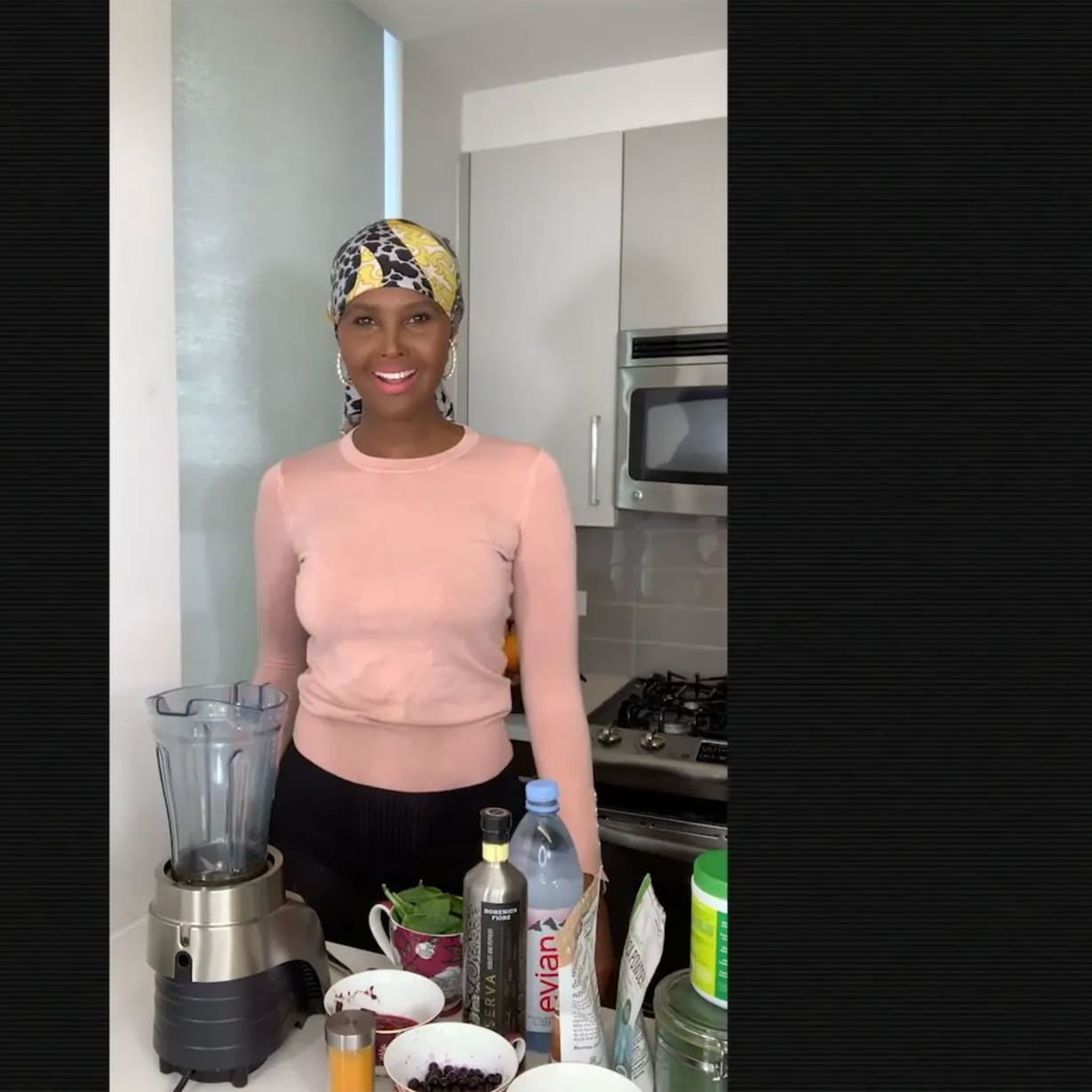 A woman in a kitchen next to a blender.