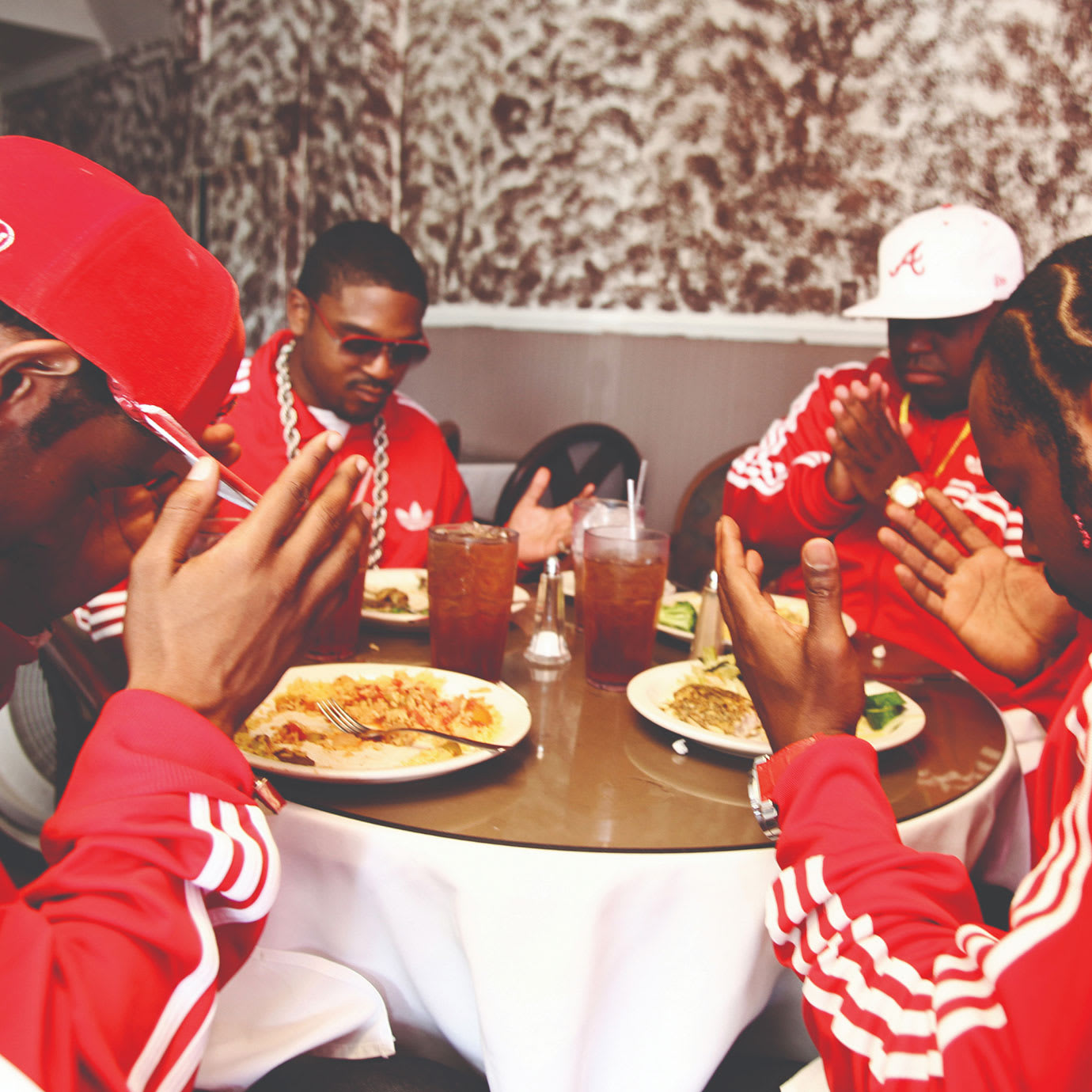 Four men in matching red tracksuits praying around a table.