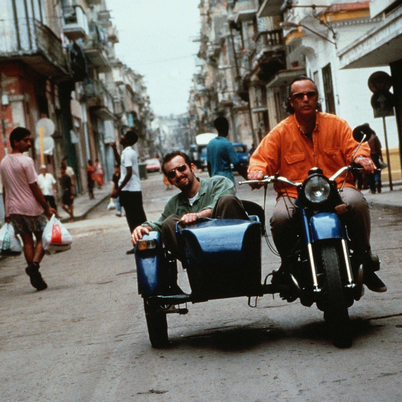 Two men on a motorbike and sidecar driving down a street.