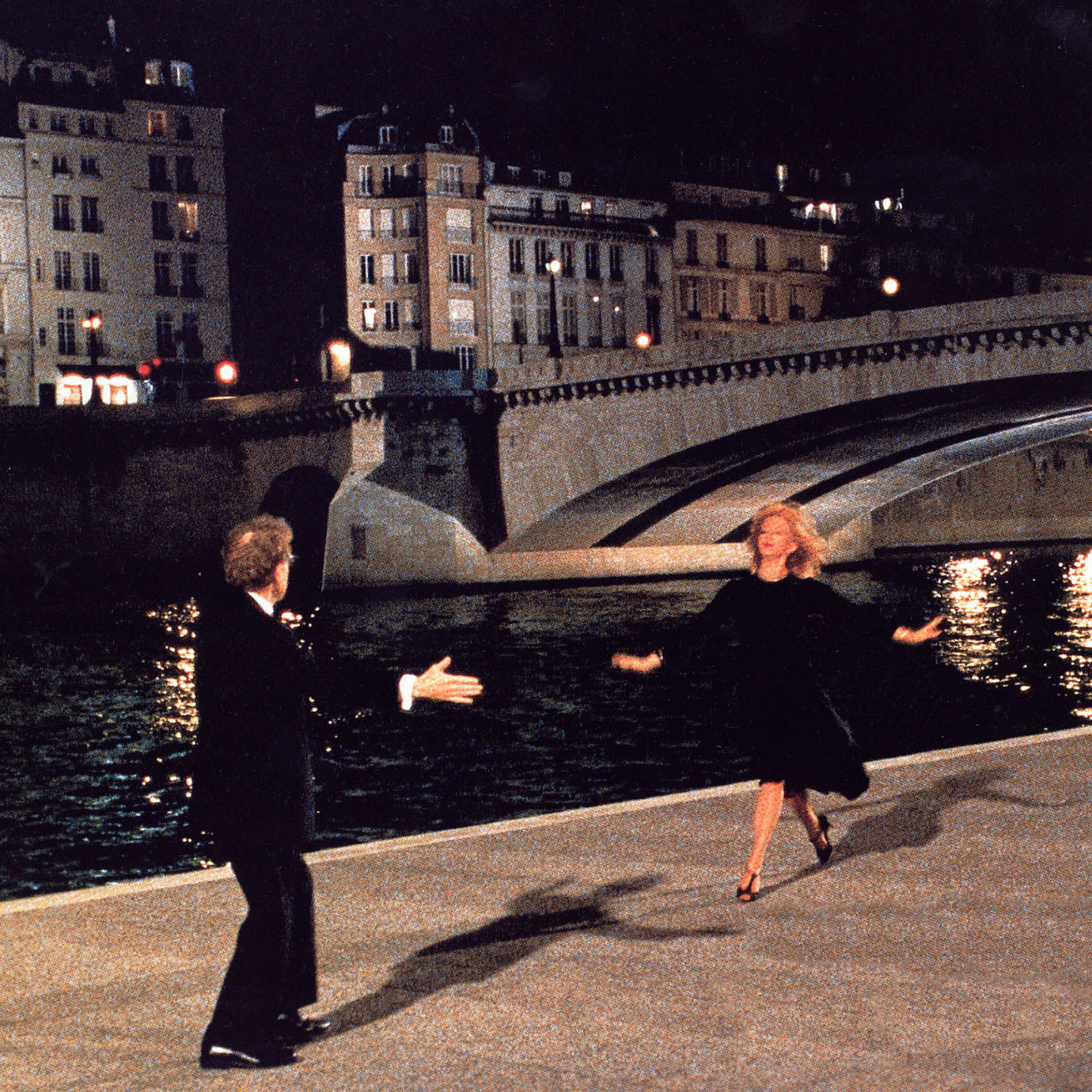A man and a woman dancing at night by a canal and bridge.