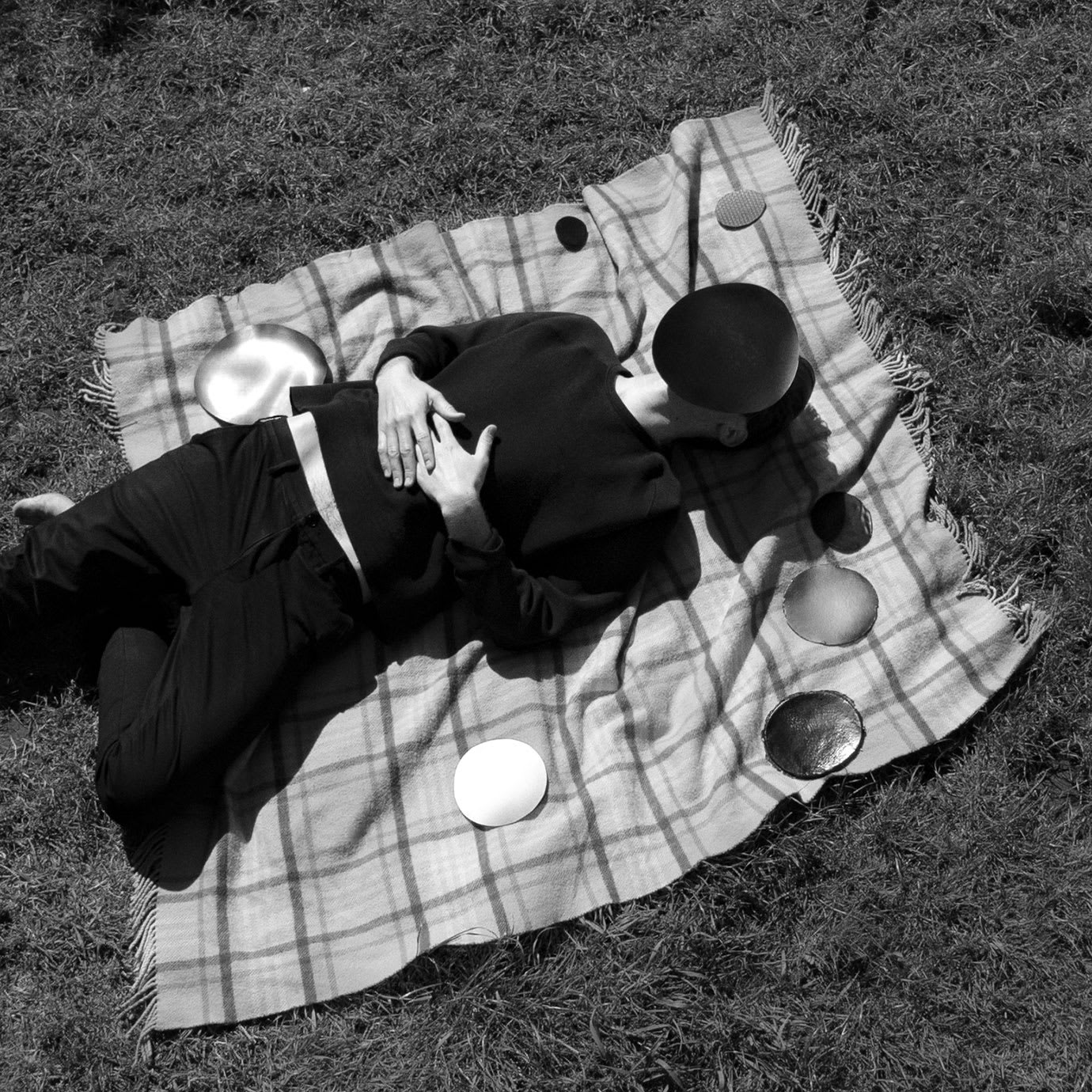 A person lying on a rug on the grass.