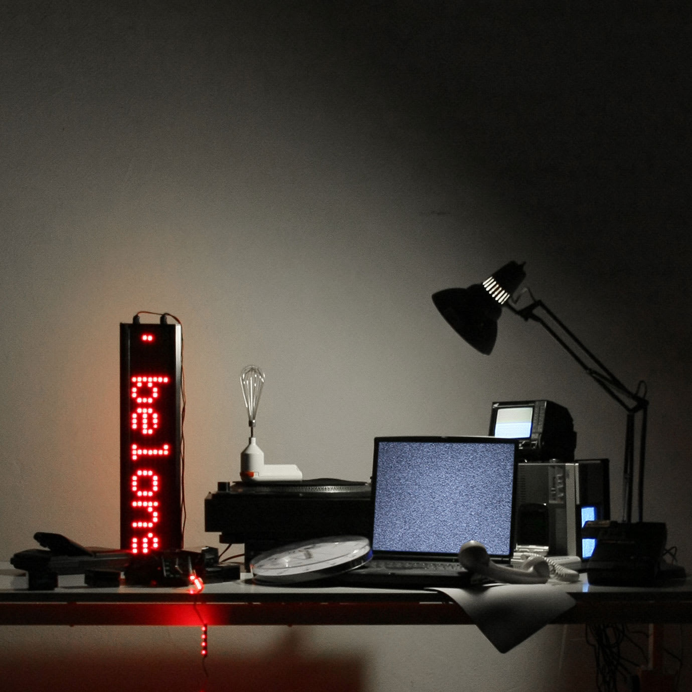 A laptop, lamp and other objects in low light.