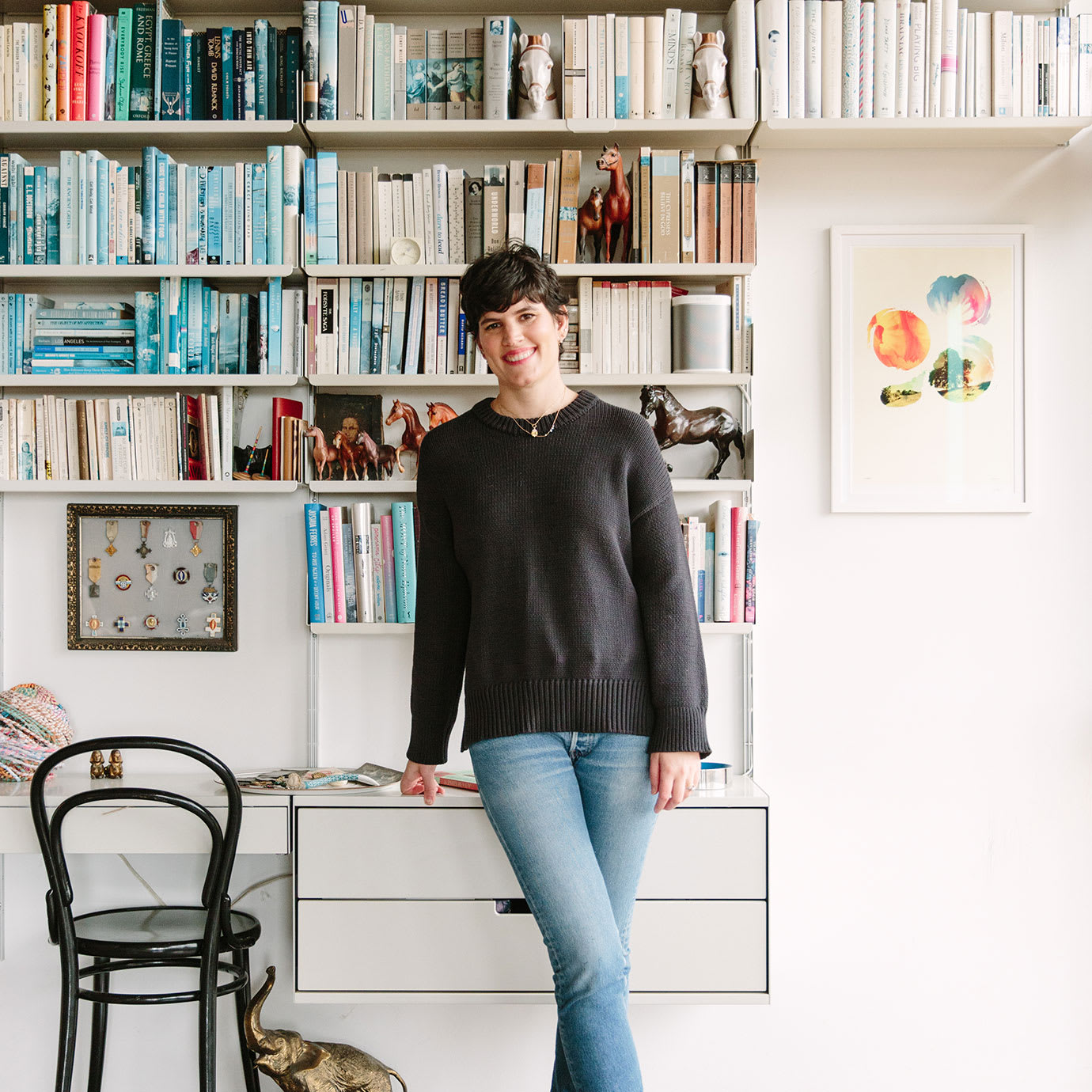 A woman standing in front of her desk and colour coordinated bookshelf.