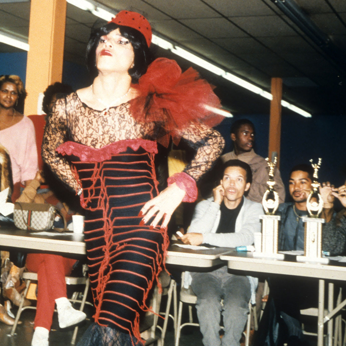 A man in drag walking during a vogueing competition.