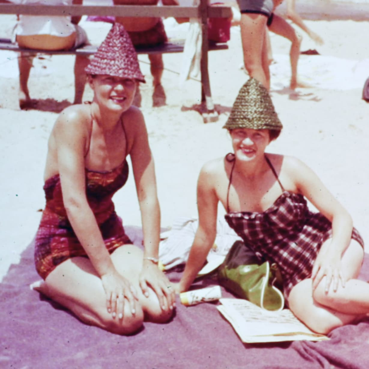 A vintage photo of two women sitting together on a beach.