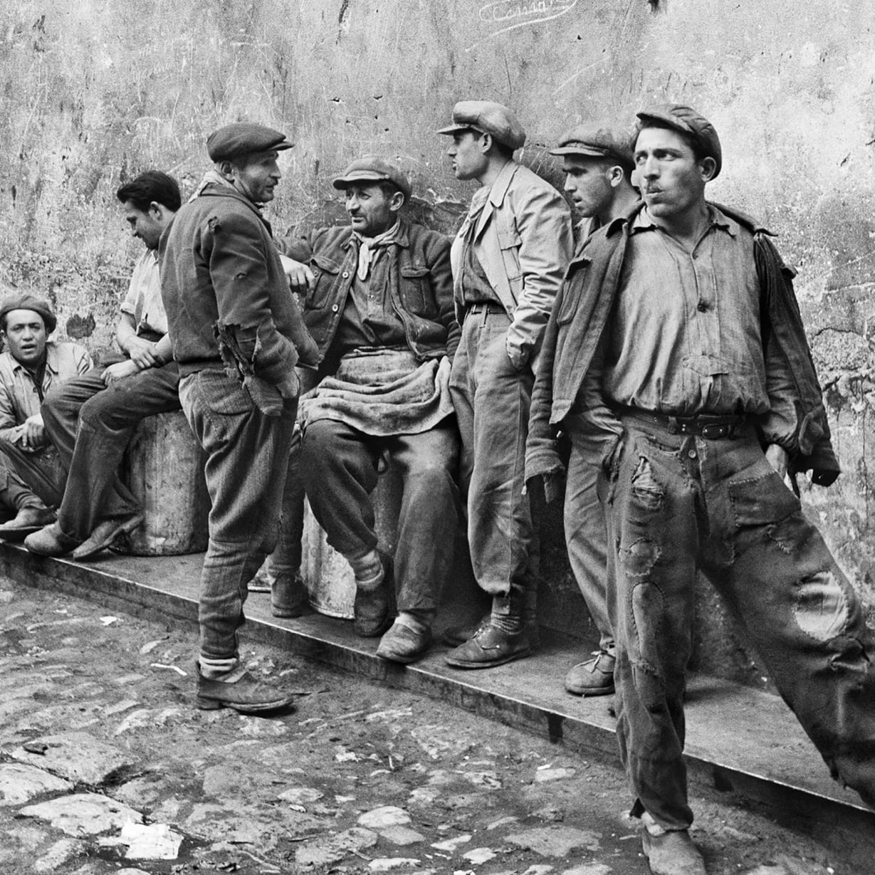 A vintage photograph of workmen standing and sitting by a wall.