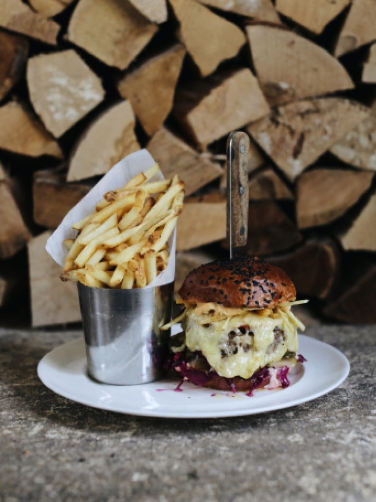 A cheese burger and a pot of chips.