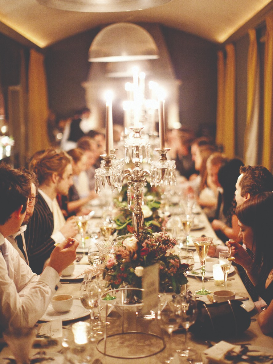Wedding guests sat around a candle lit dinner table.
