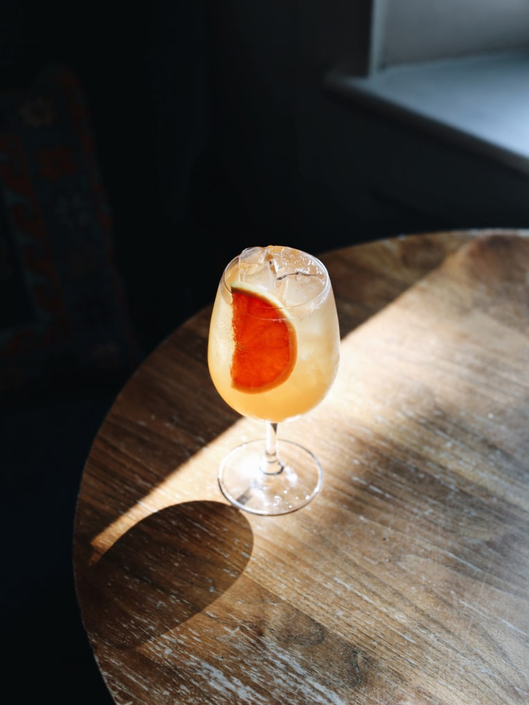 A cocktail on a wooden table in the sunlight.
