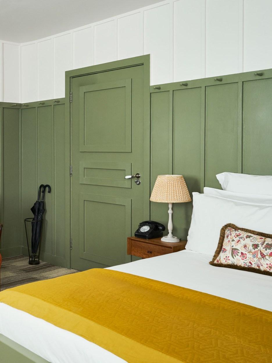 The corner of a green bedroom.