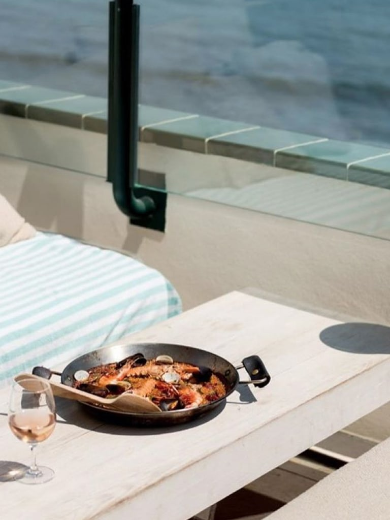 A pan of paella on a table next to the sea.