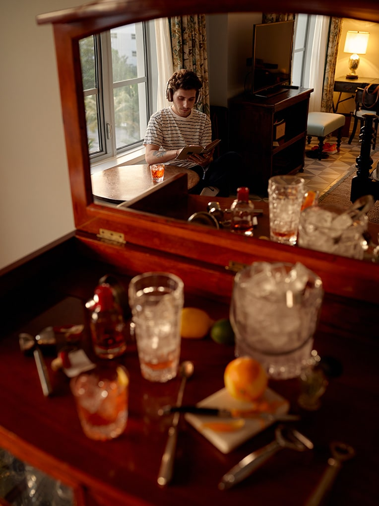 A man reading a book whilst listening to headphone reflected in the mirror of a drinks cabinet.