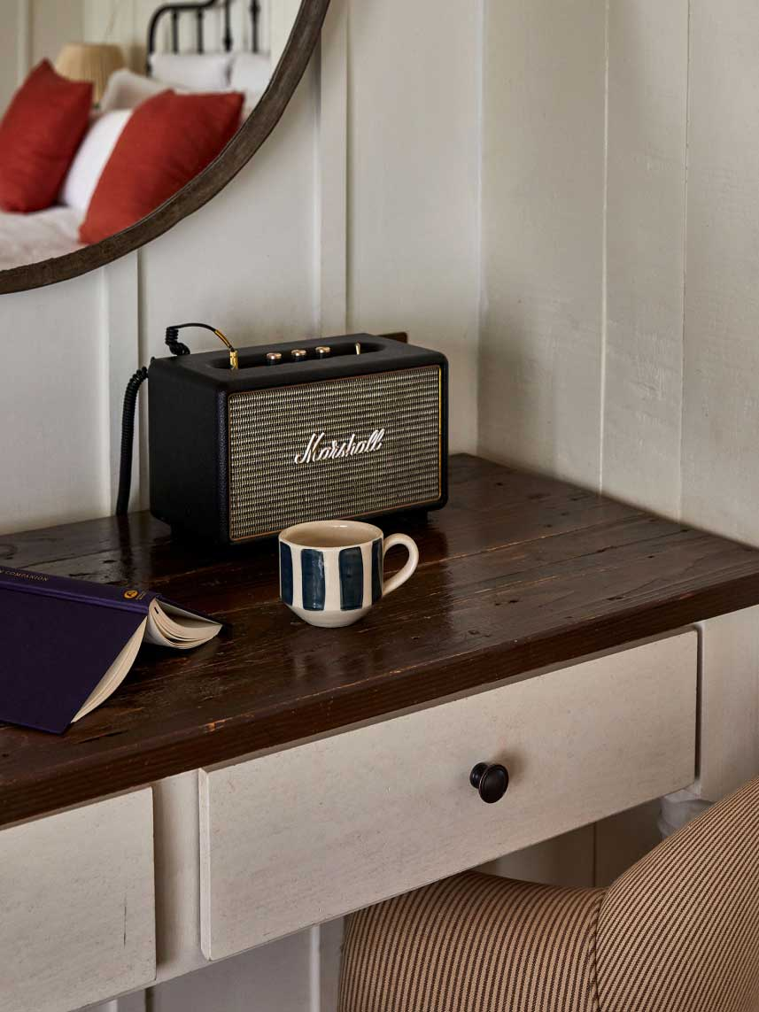 A speaker, mug and open book on a dresser surface.