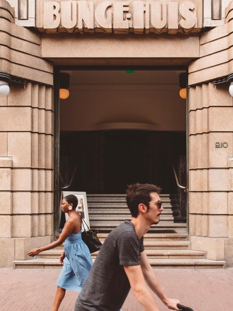 A man and woman walking passed the entrance of a building called Bungehuis.