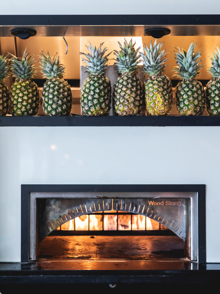 A pizza oven with pineapples on a shelf above it.