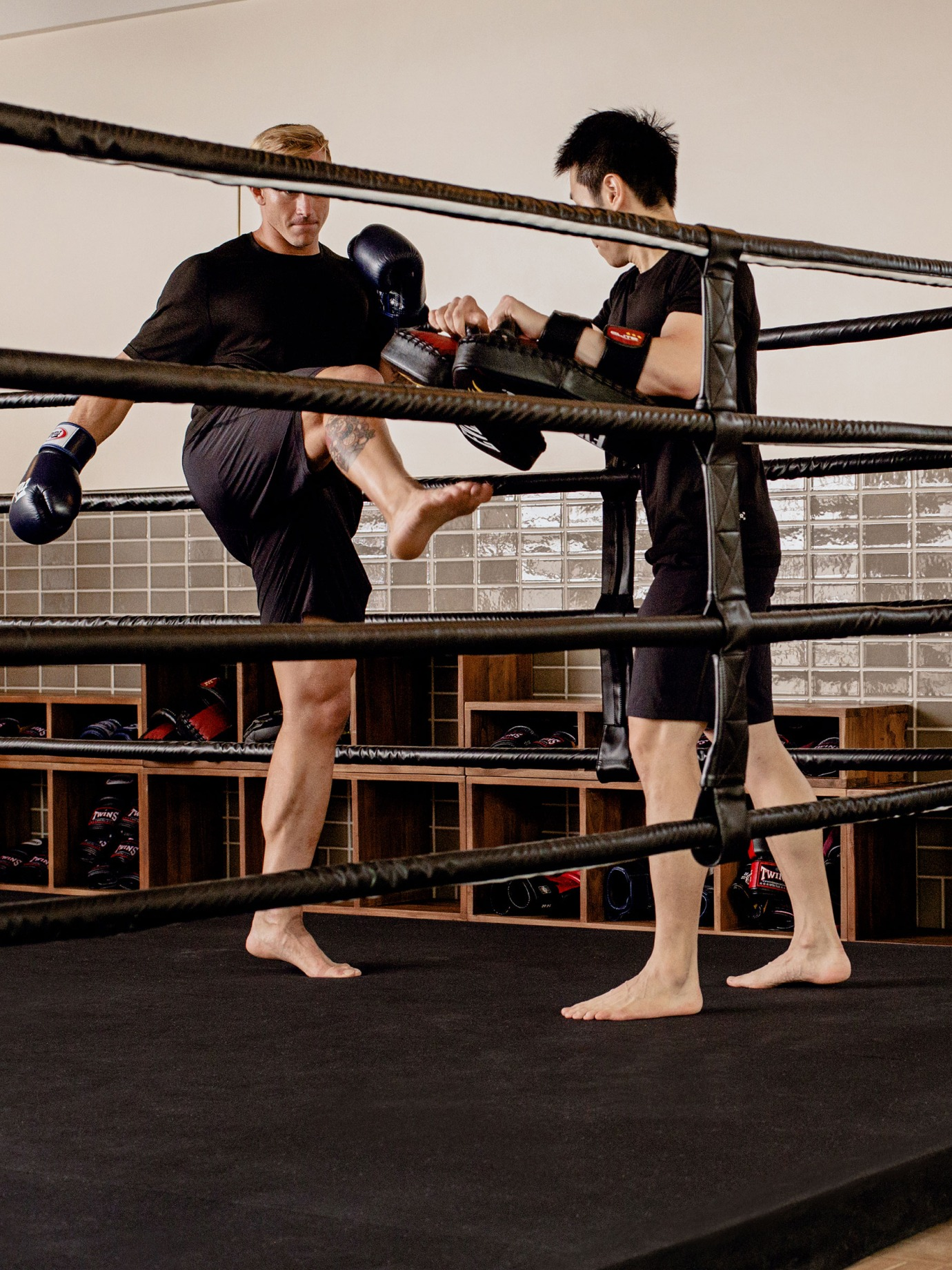 Two men at a kickboxing lesson in a boxing ring.