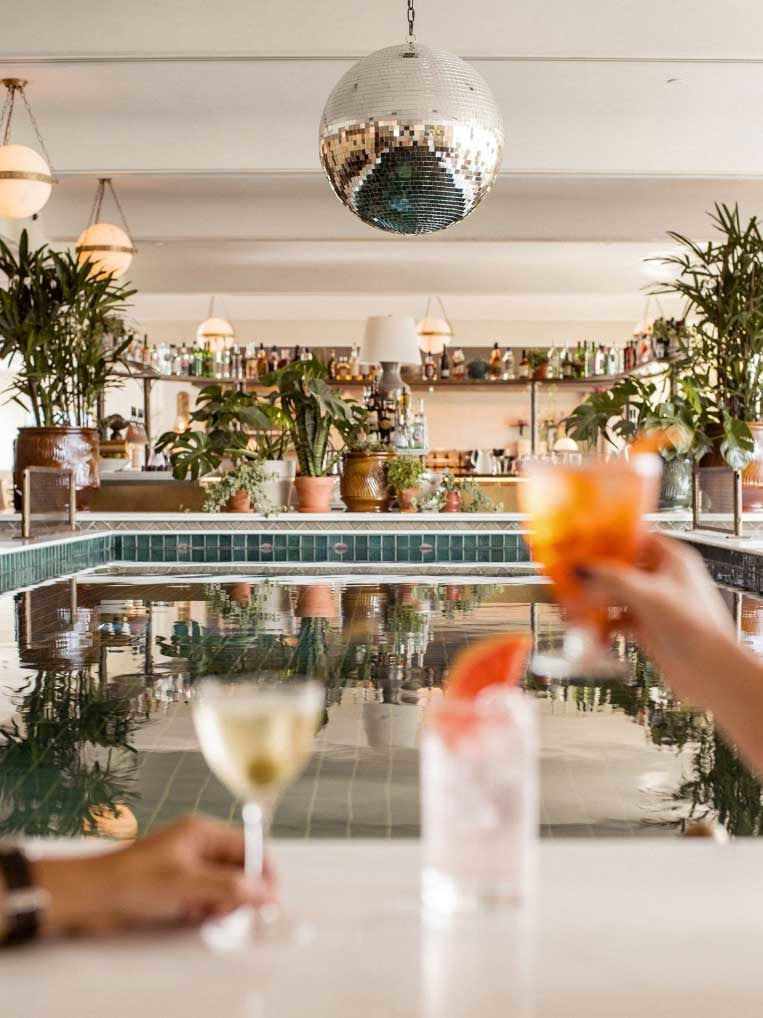 Two hands holding cocktails in front of an indoor pool.