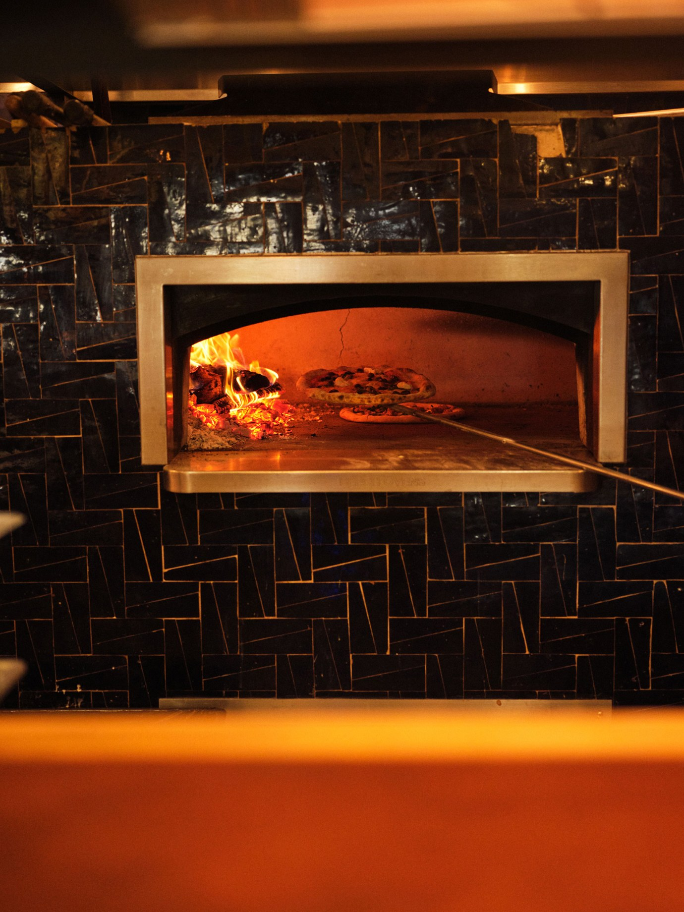 A pizza is cooked in a pizza oven.