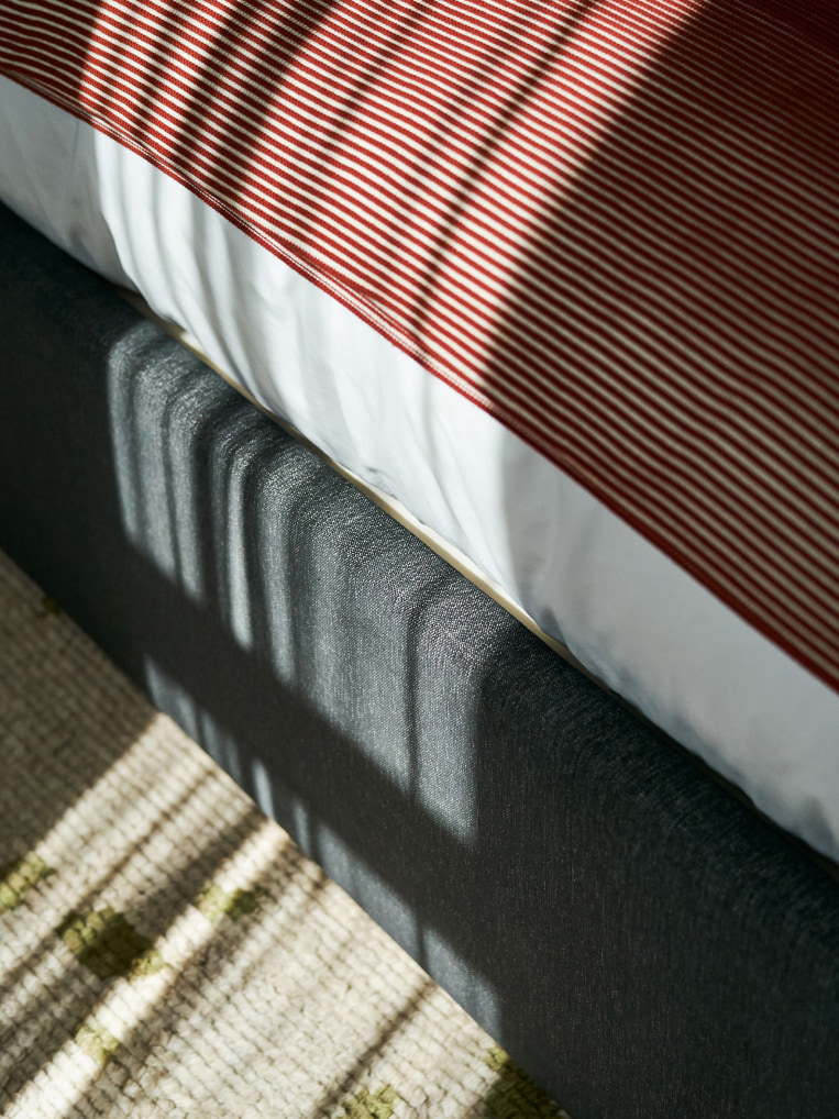 Light falls on the end of a bed.