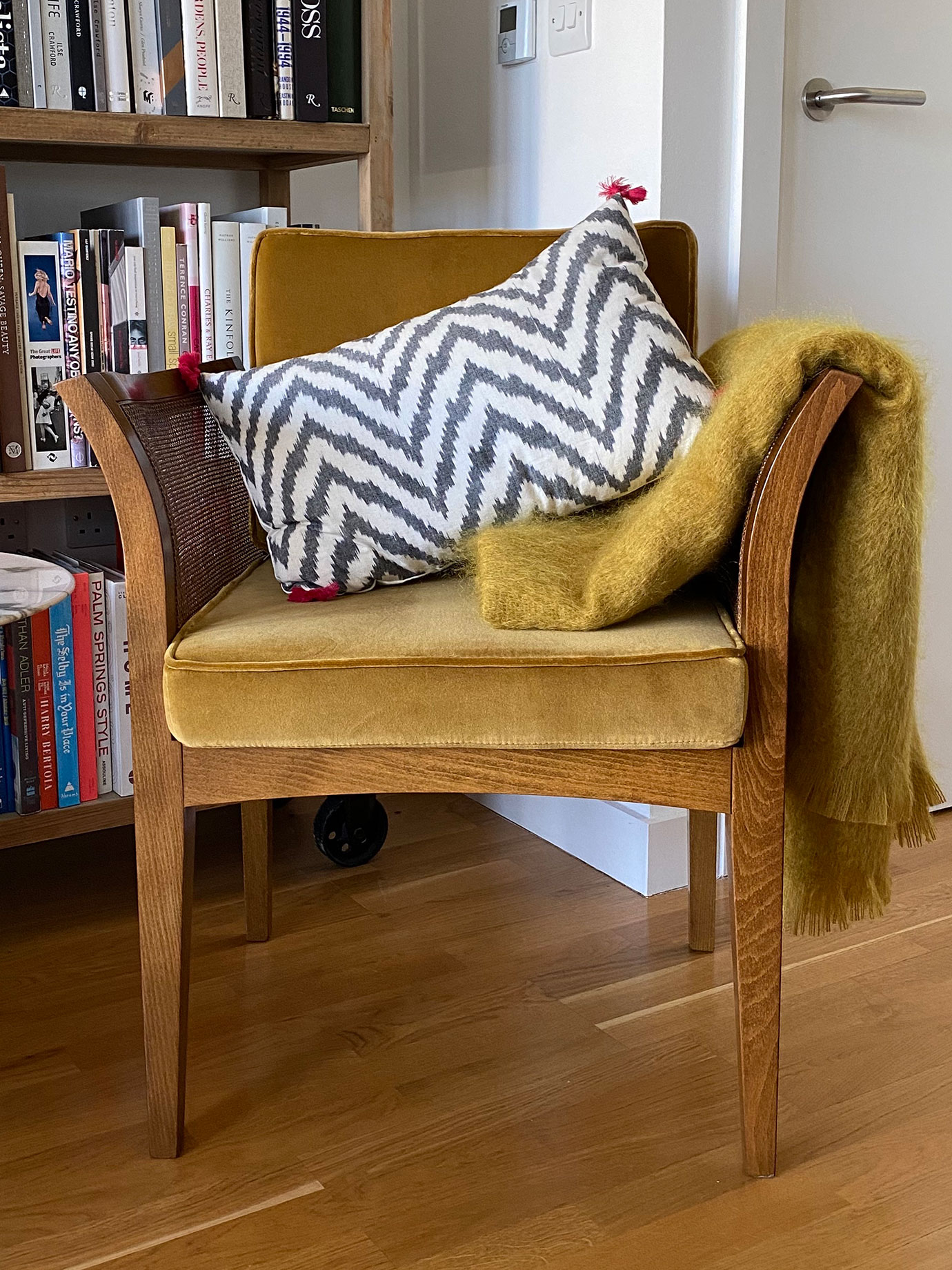 A wooden chair with a cushion and a throw on it.