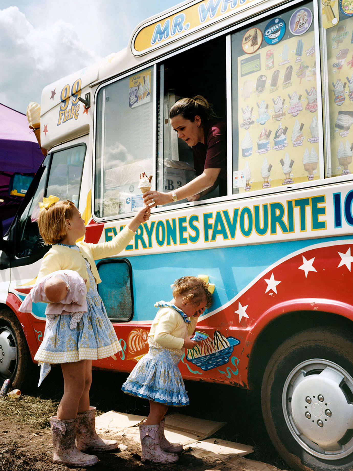 Two children being served ice cream from a van.
