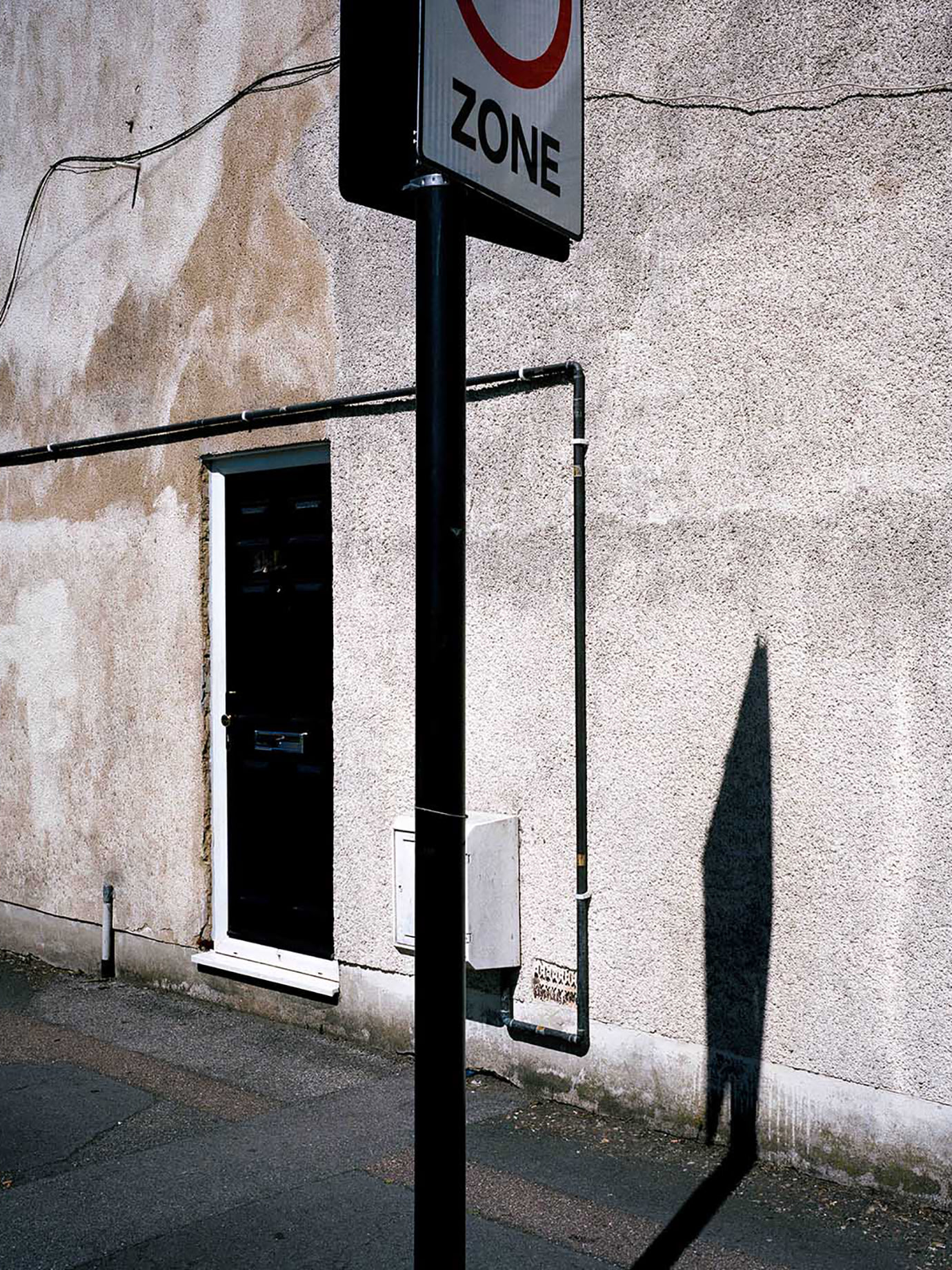 A street sign casting a shadow on a wall.