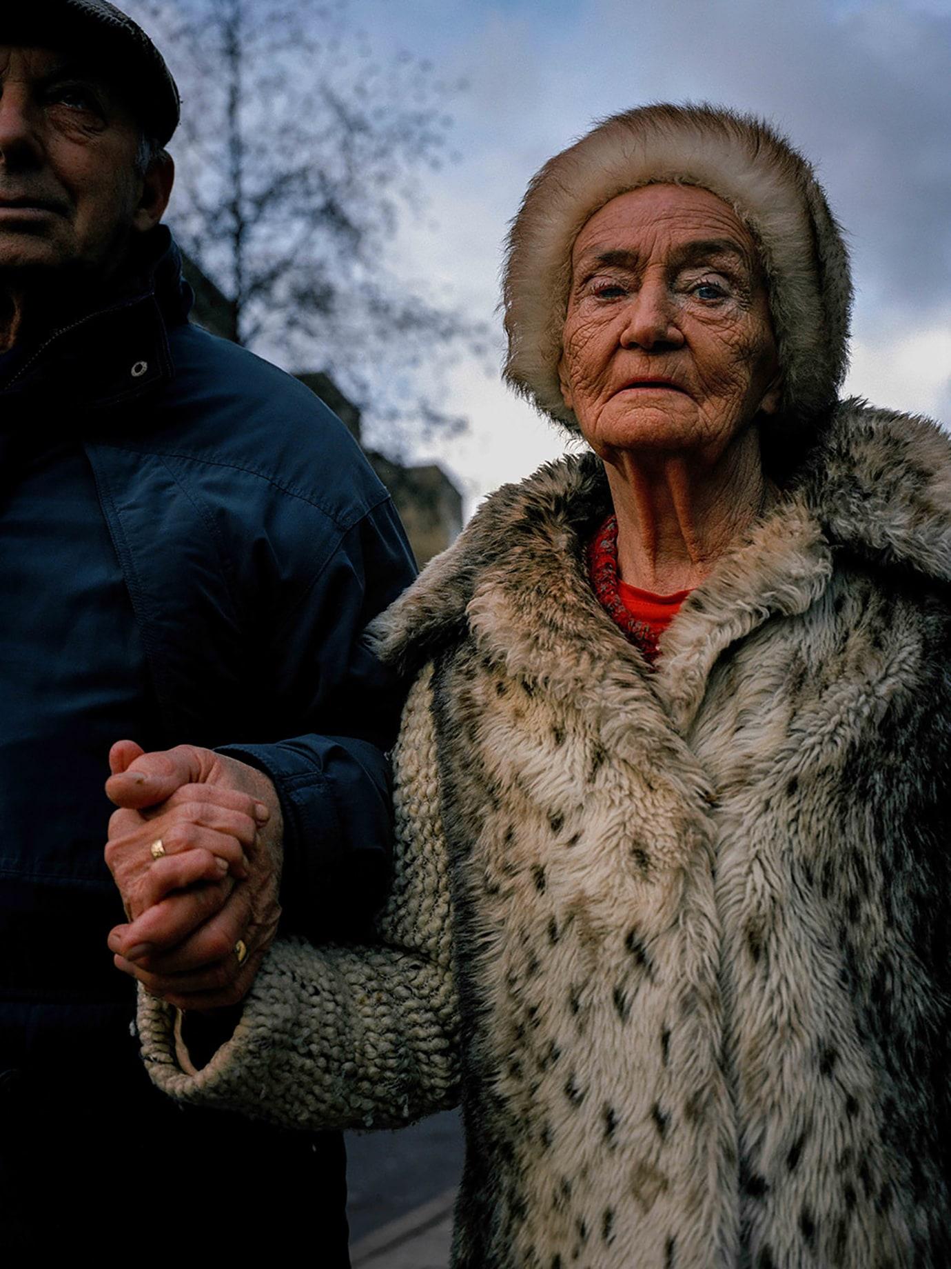 An elderly couple arm in arm.
