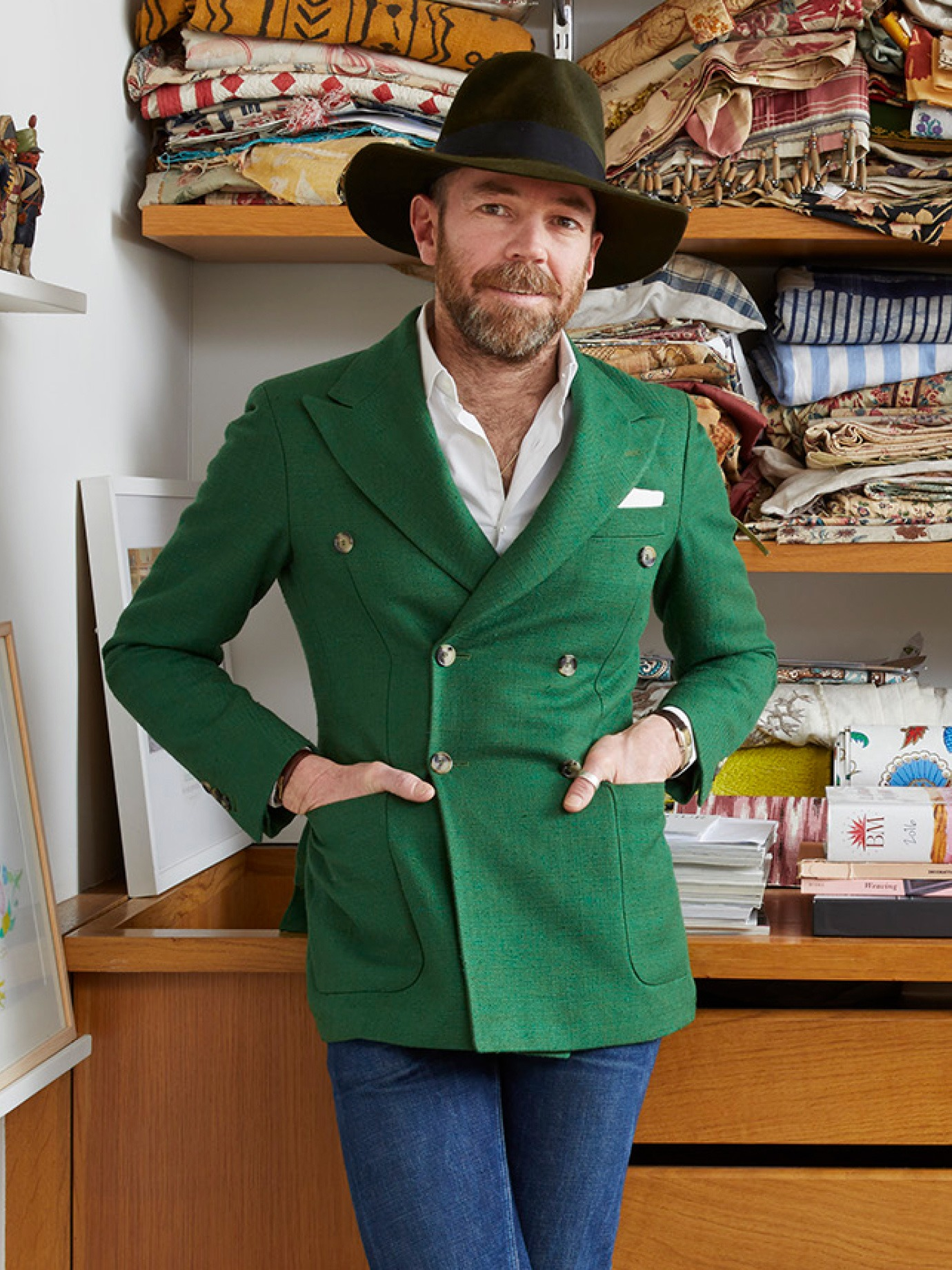A man in a broad hat and green jacket leaning against a cabinet containing swatches.