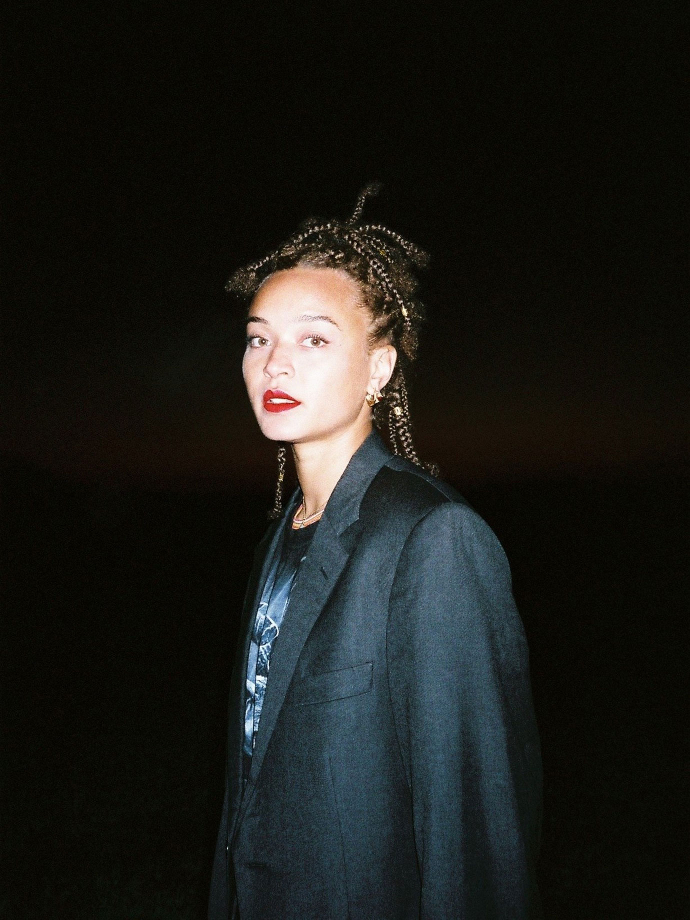 A woman wearing a suit jacket at night.