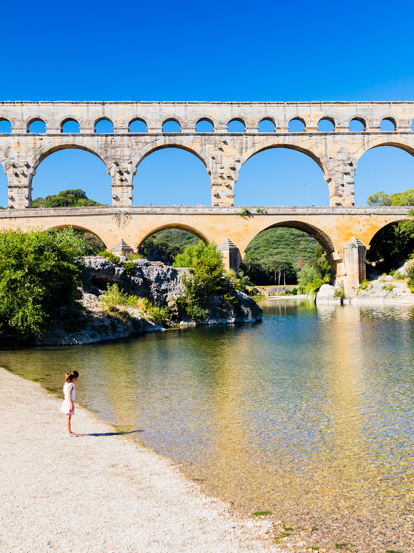 A child standing on the shore of a river with an aqueduct in the background.