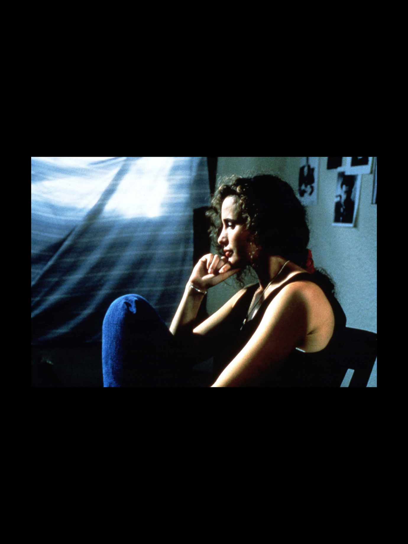 A woman sitting against a wall in a coldly lit room.