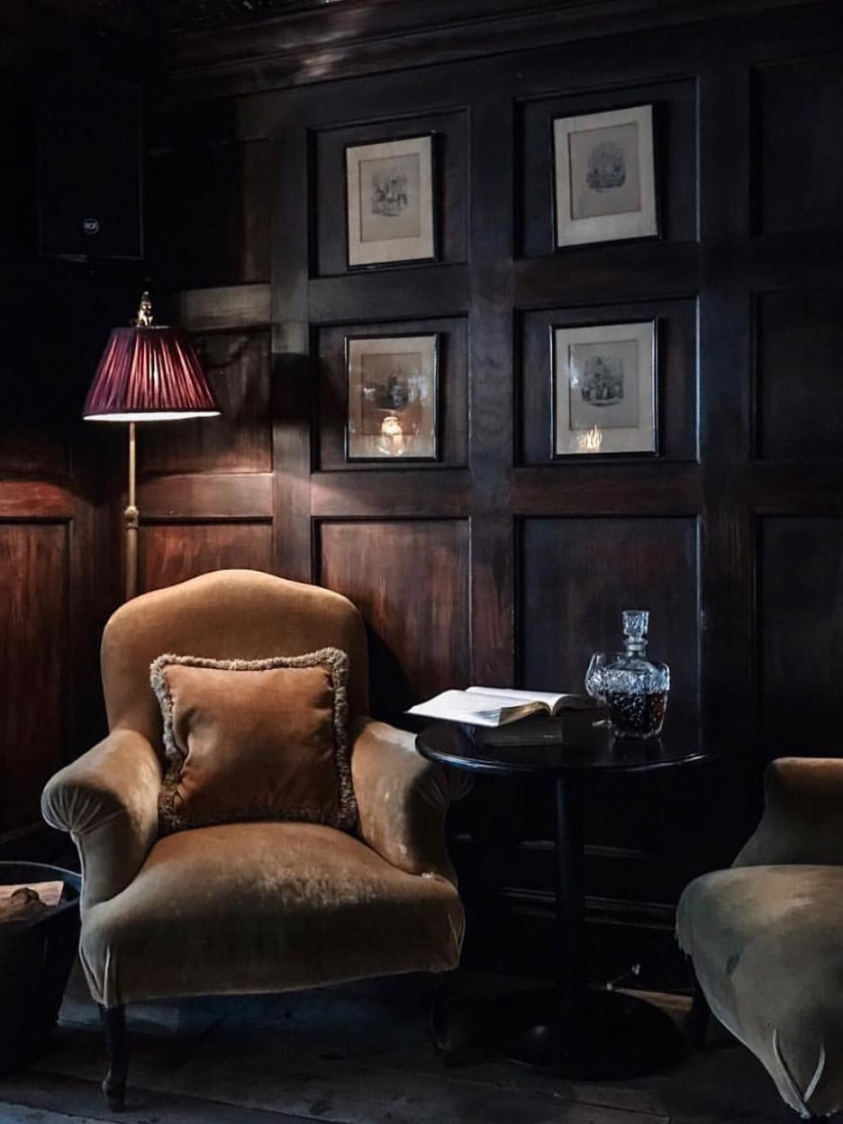 A corner of a wood panneled room with a floor lamp and an armchair.