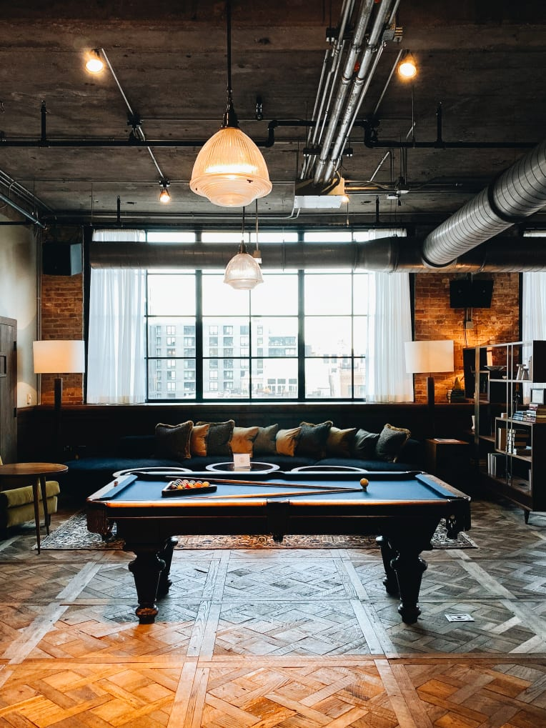 A pool table in warehouse type space.