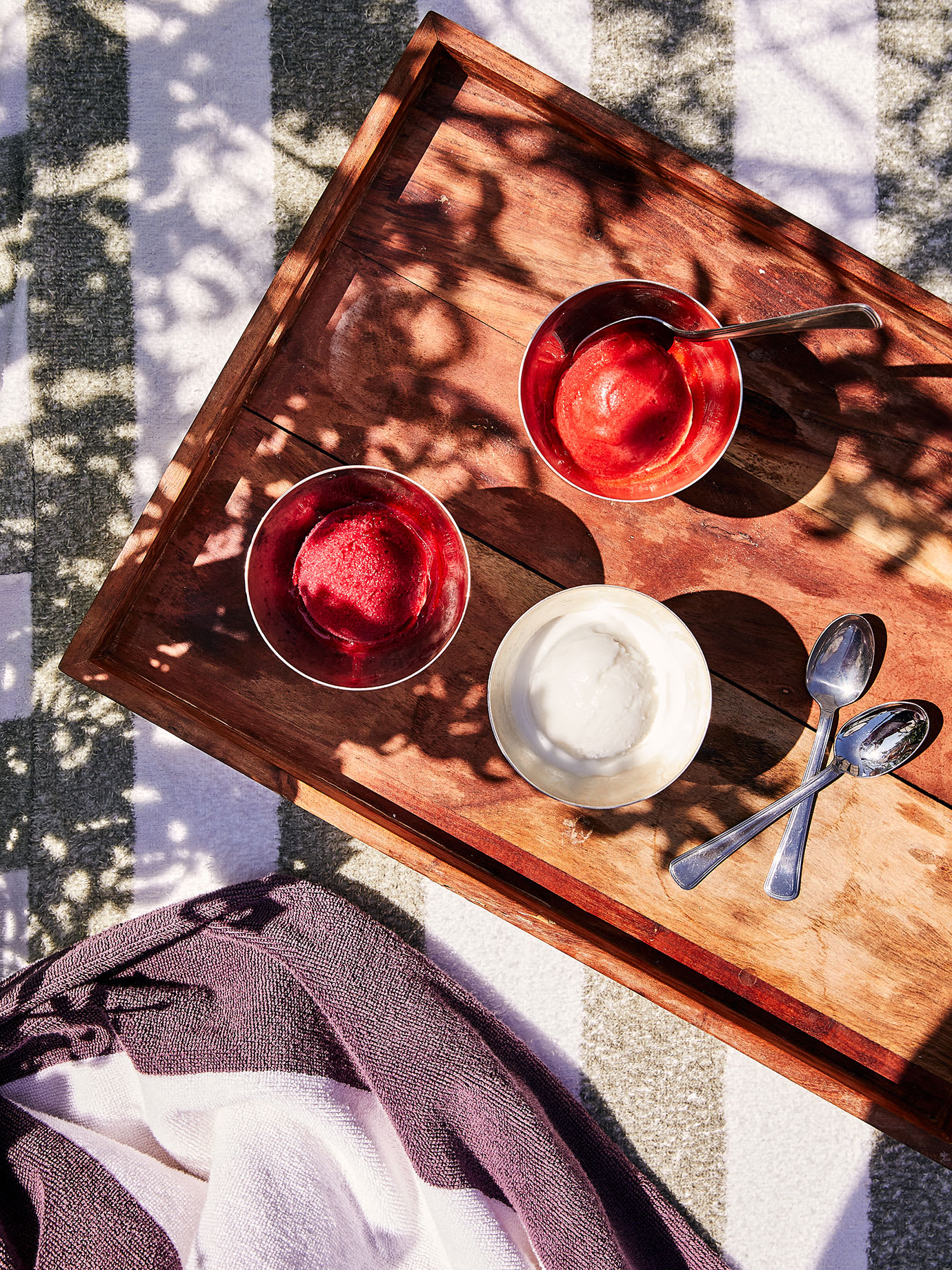 Three types of sorbet in metal bowls on a tray.