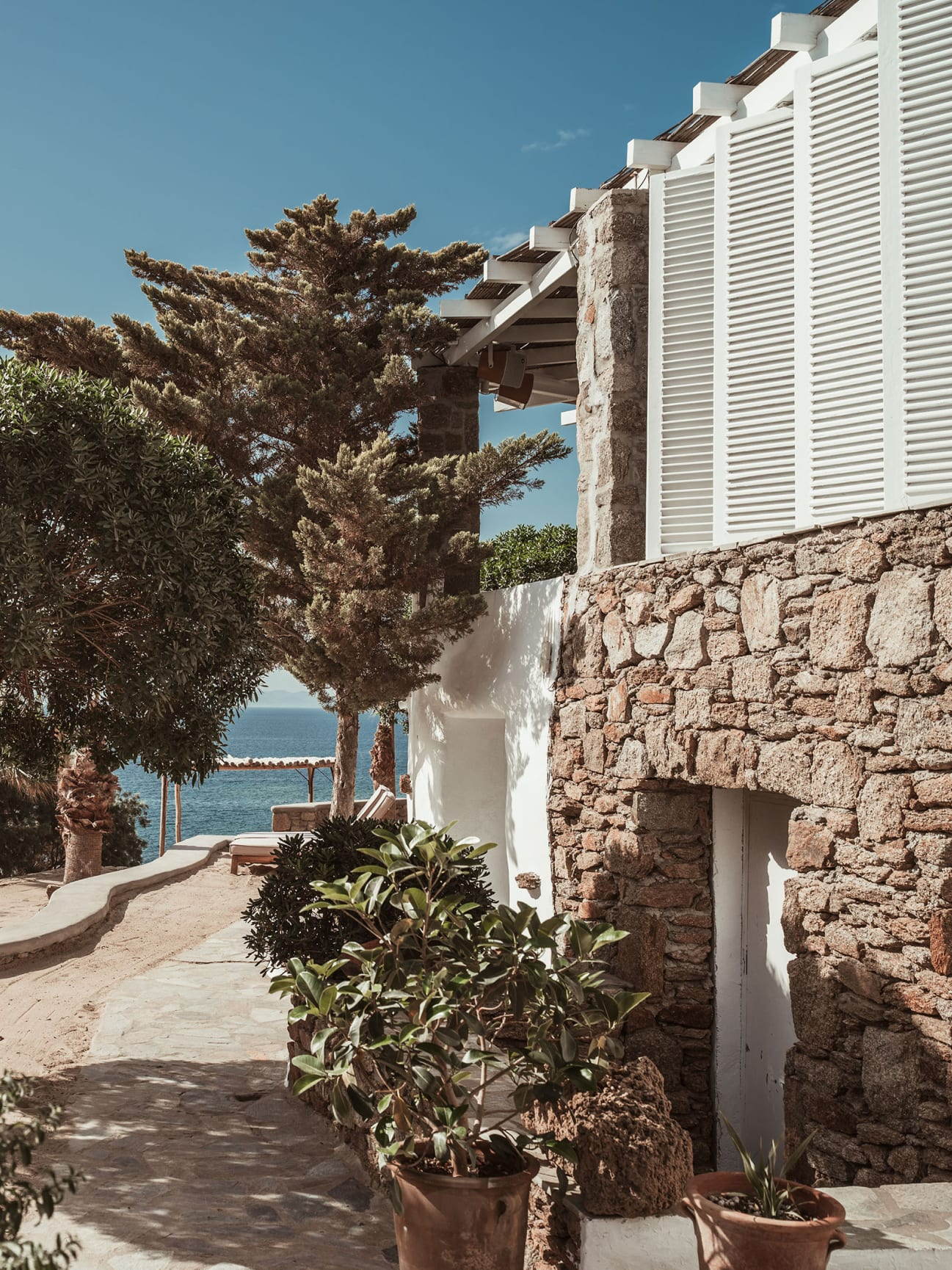 The exterior of a building with trees and the sea in the background.