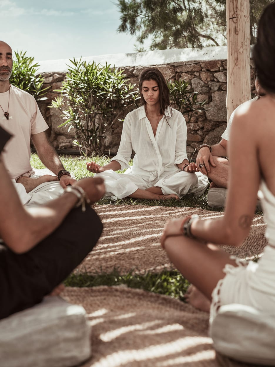 Men and women meditating in a circle.