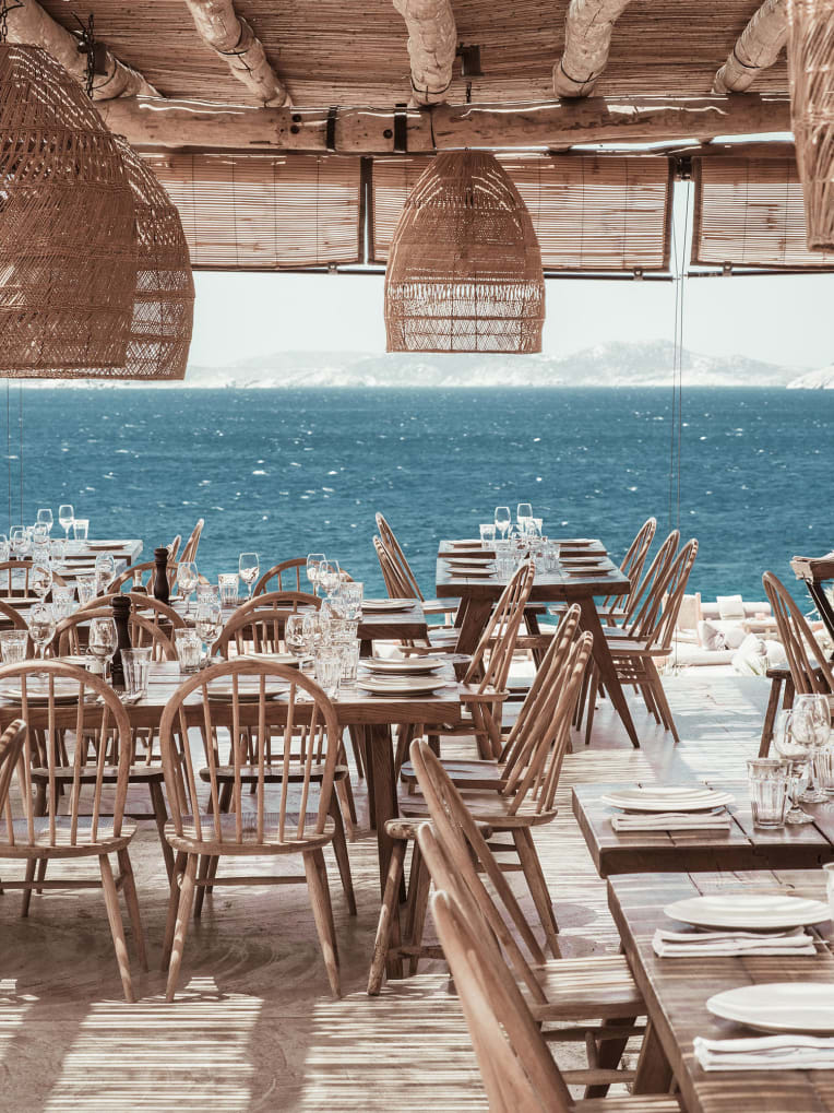 A covered outdoor restaurant overlooking the sea.