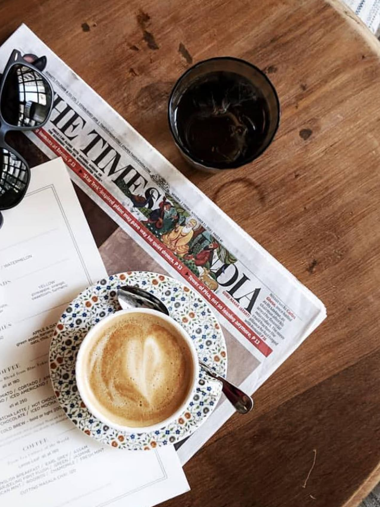A coffee and a copy of the The Times of India newspaper on a table.