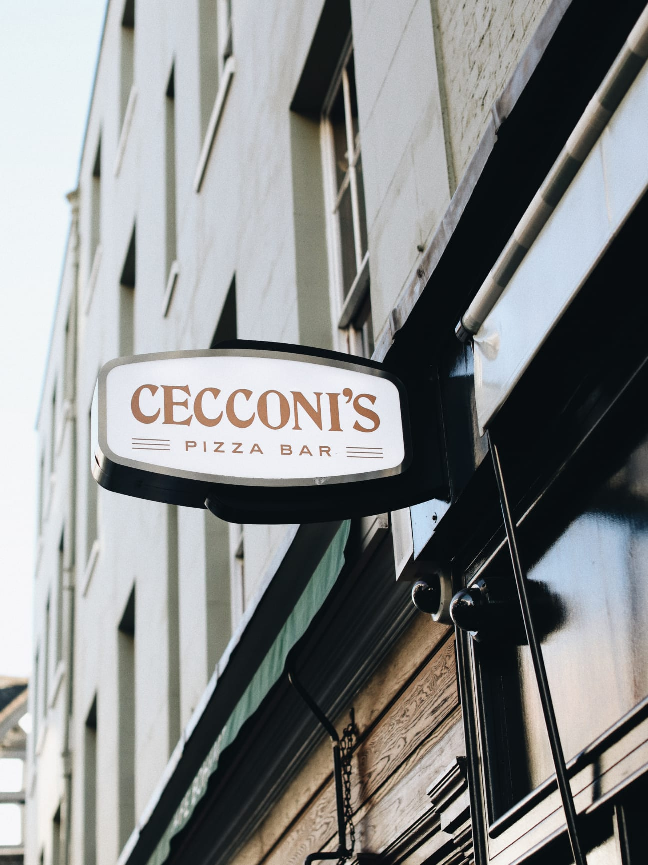 The exterior of a restaurant with a sign saying Cecconis Pizza Bar protruding from its wall.